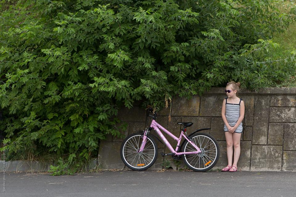 Flicka med cykel vid vägkant