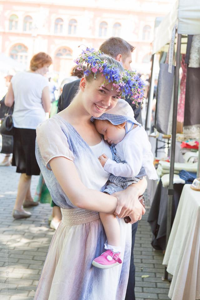 Kvinna med blomsterkrans och sovande barn