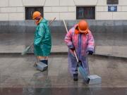 Renhållningsarbetare med regnskydd